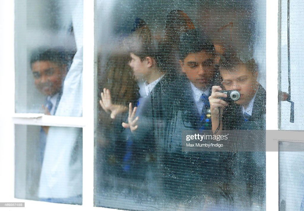 Students at Northolt High School peer through a steamed up window to get of view of Catherine, Duchess of Cambridge as she opens The ICAP Art Room on February 14, 2014 in Ealing, England.