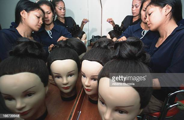 Students at Sapor's Modeling School practice hairdressing technique during class