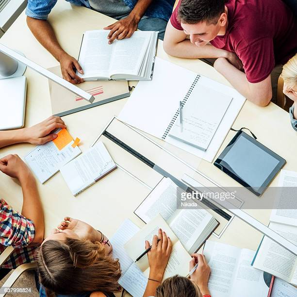 students at table with books in classroom