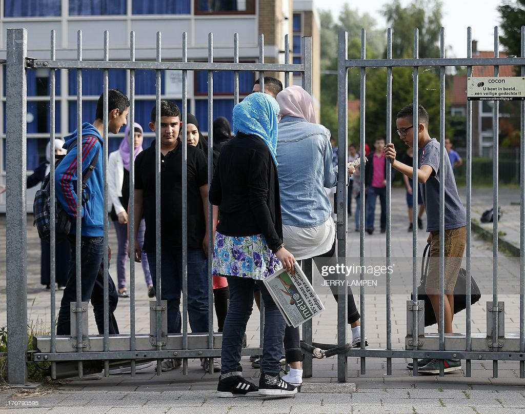 Students at the Ibn Ghaldoun Islamic School in Rotterdam enter on June 18, 2013 through the fence the only Islamic secondary school in the Netherlands, which is obstructed by a padlocked chain allegedly placed there by members of the right-wing group Identitair Verzet, who reportedly do not want students to retake exams this week after thieves stole copies of the national tests for 24 courses. AFP PHOTO / ANP / JERRY LAMPEN - netherlands out -