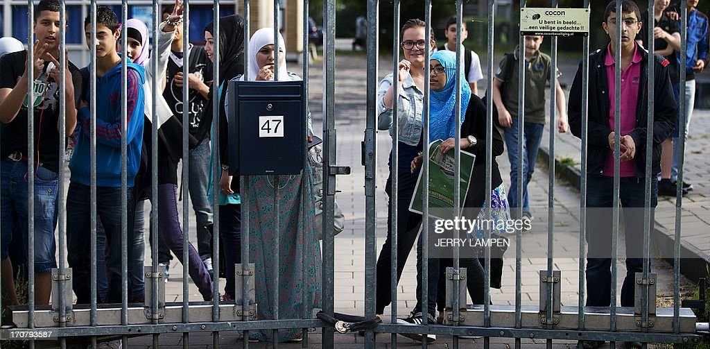 Students at the Ibn Ghaldoun Islamic School in Rotterdam look on June 18, 2013 through the fence of the only Islamic secondary school in the Netherlands, which is obstructed by a padlocked chain allegedly placed there by members of the right-wing group Identitair Verzet, who reportedly do not want students to retake exams this week after thieves stole copies of the national tests for 24 courses. AFP PHOTO / ANP / JERRY LAMPEN - netherlands out -