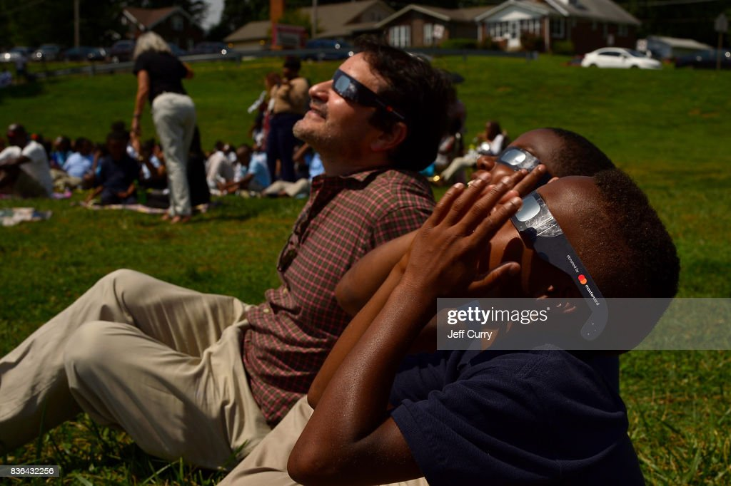 Students at the Jennings School District view the solar eclipse with Edgar Aguilar of Mastercard on August 21, 2017 in St Louis, Missouri.