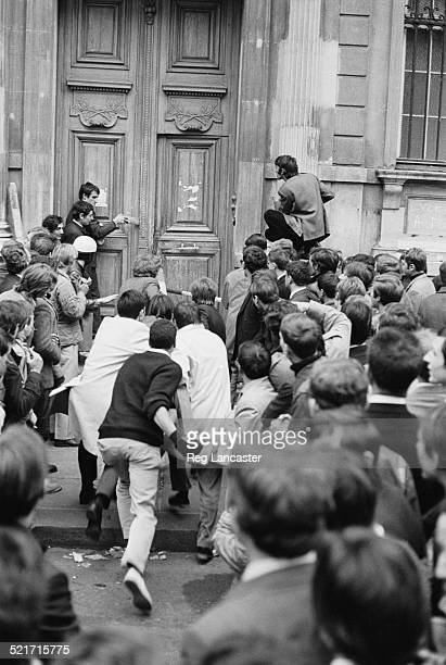 Students attempt to knock through the door of a building during civil unrest in Paris France 30th May 1968