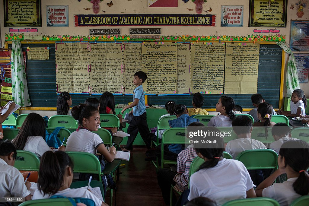 Students attend class at the San Fernando Central School on August 15, 2014 in Tacloban, Leyte, Philippines. The school was heavily damaged during Typhoon Yolanda and currently still has evacuated families living temporary housing in some classrooms. Residents of Tacloban city and the surrounding areas continue to focus on rebuilding their lives nine months after Typhoon Haiyan struck the coast on November 8, 2013, leaving more than 6000 dead and many more homeless. With many businesses and government operations back up and running and with the recent start of the years typhoon season, permanent housing continues to be the main focus with many families still living in temporary accommodation. As well as continuing recovery efforts Leyte is preparing for the arrival of Pope Francis, who will visit the region from January 15- 19.