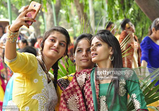 Students attired in traditional dresses taking selfie during Teej festival celebrations at GCG on August 17 2015 in Ludhiana India Teej refers to the...