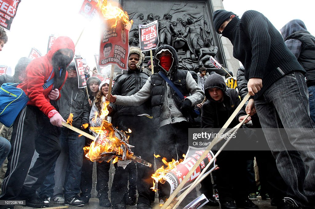Students burn a placard featuring David Cameron's face as they take part in a protest over the Government's budget cuts and proposed rise in tuition fees on November 30, 2010 in London, England. Hundreds of students evaded police containment tactics and marched throughout Westminster and the City of London from Trafalgar Square in the third major protest of its kind in London in as many weeks.