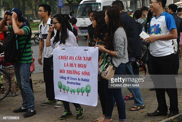 Students carry a poster as they join a rally protesting against a treefelling plan by the municipal authorities in Hanoi on March 22 2015 Vietnam...