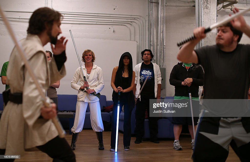 Students Chandra Gilmore, Carol Wong and Ernesto Altamirano look on during a demonstration of combat moves with lightsabers during a Golden Gate Knights class in saber choreography on February 24, 2013 in San Francisco, California. Star Wars fans Alain Bloch and Matthew Carauddo founded the Golden Gate Knights in 2011 to teach classes on how to safely wield a lightsaber and perform choreographed moves. The three hour class costs ten dollars and all equipment is provided.