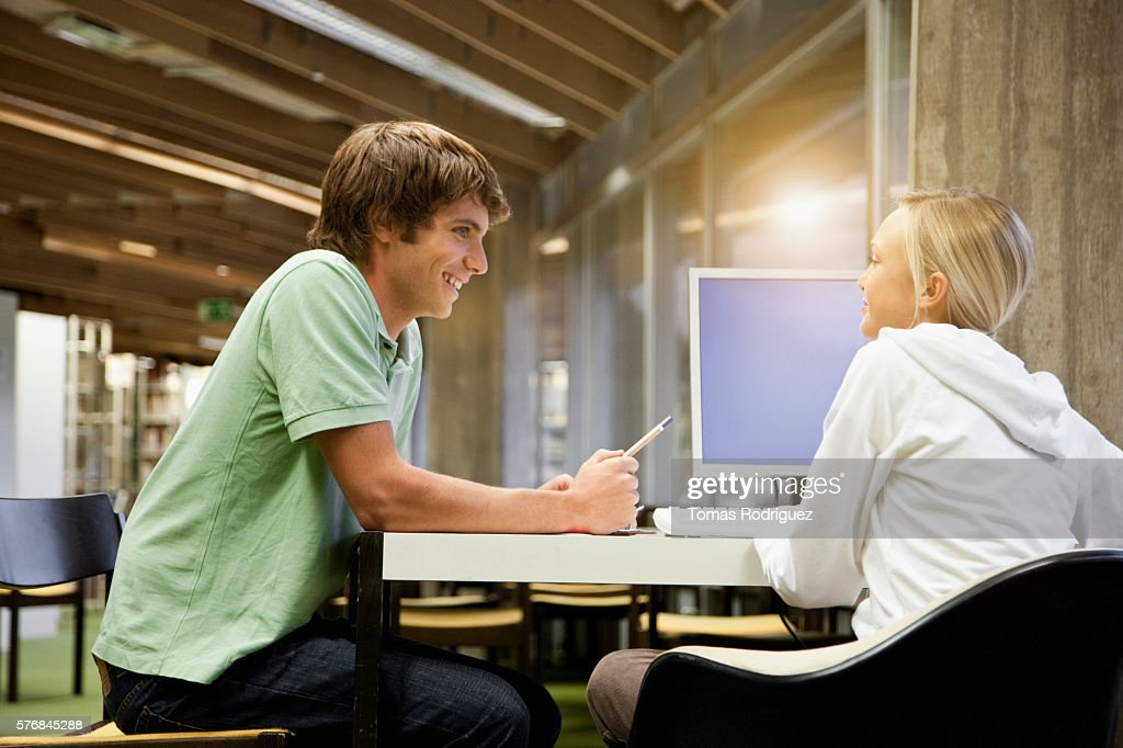 Students chatting in library : Bildbanksbilder