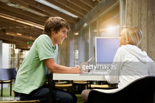 Students chatting in library : Stock Photo