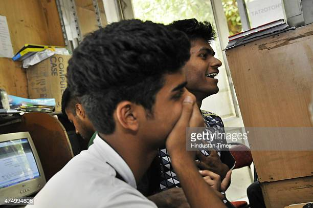 Students check their Class 10 result of CBSE examination in a cyber cafe at Gol Market on May 28 2015 in New Delhi India Over 13 lakh students...