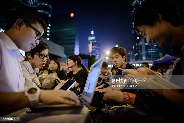 Students check their laptops and smartphones during a rally of prodemocracy demonstrators in Hong Kong on October 10 2014 Hong Kong's democracy...