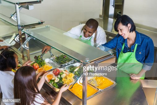 Students choosing healthy food in school cafeteria lunch line