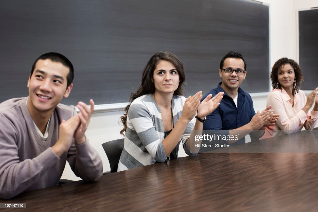 Students clapping in classroom : Stock Photo