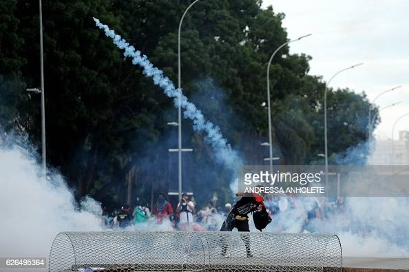 TOPSHOT Students clash with police during a protest in front of the Congress in Brasilia against the bill that freezes government spending for 20...