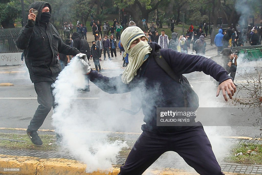 Students clash with riot police during a march held to protest the slow pace of educational reform, in Santiago, on May 26, 2016. / AFP / CLAUDIO