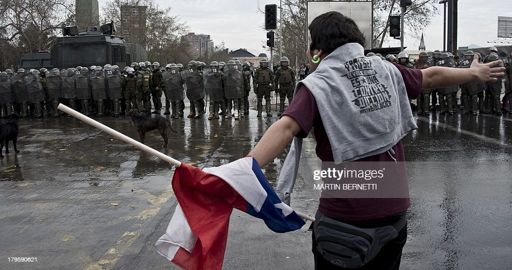 Students clash with riot police during a protest to demand Chilean President Sebastian Pinera's government an intensive educational reform and to break with other legacies of the dictatorship of Augusto Pinochet (1973-1990), in Santiago, on September 5, 2013. AFP PHOTO/MARTIN BERNETTI