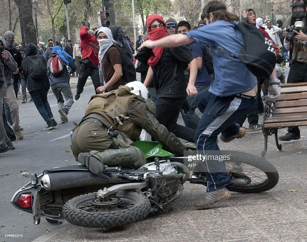 Students clash with riot police during a protest to demand Chilean President Sebastian Pinera's government an intensive educational reform and to break with other legacies of the dictatorship of Augusto Pinochet (1973-1990), in Santiago, on September 5, 2013. AFP PHOTO/Claudio SANTANA