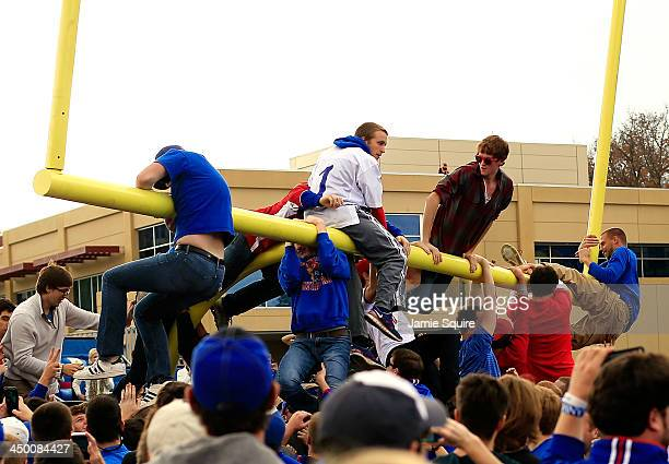 Students climb on and dismantle the goalposts after Kansas defeated the West Virginia Mountaineers 3119 to win the game at Memorial Stadium on...