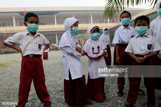 Students cover their face with masks due to smoke from peat forest fire in Aceh Indonesia on July 25 2017 The number of hotspots in Indonesia...
