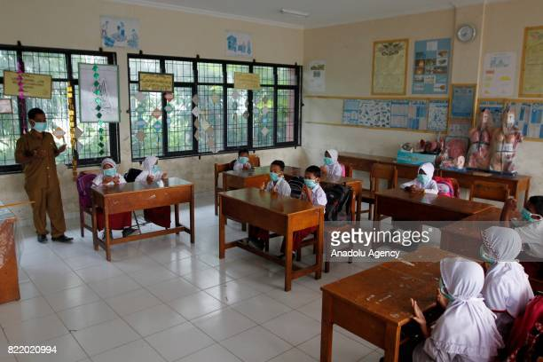 Students cover their face with masks due to smoke from peat forest fire as they attend a class in Aceh Indonesia on July 25 2017 The number of...