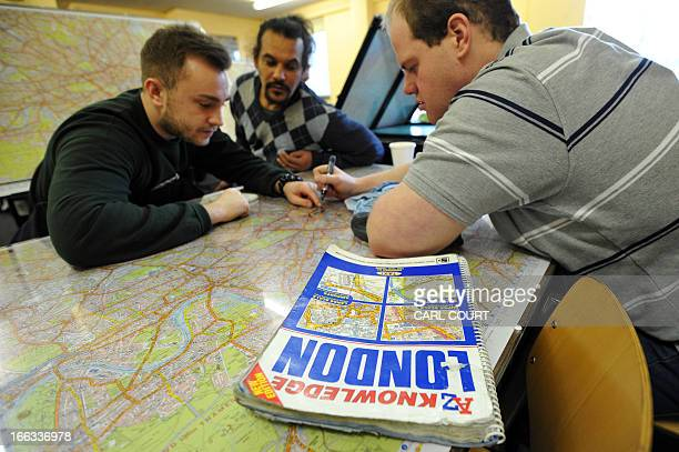 Students discuss routes over a map of London in a test centre in north London on February 28 2013 All London Black Cab drivers are required to pass...
