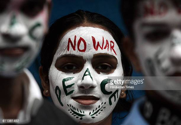 Students display peace messages painted on their faces during an antinuclear demonstration to mark the 63rd anniversary of the atomic bombing of...