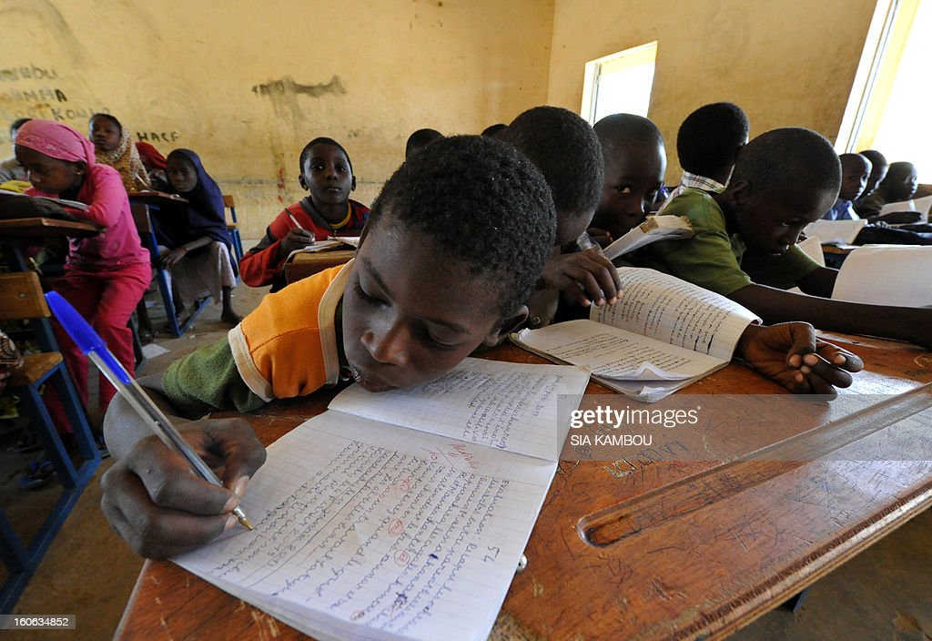 Students do work in a classroom in Gao, in the north of Mali, on the first day of the reopening of schools after the French bombing of Islamist targets, on February 4, 2013. Schools reopened today in Gao after the town was taken on January 26 by French and Malian forces from Islamists who had been occupying it for the last year. AFP PHOTO / SIA KAMBOU