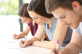 Close up of three concentrated students doing an exam in a classroom