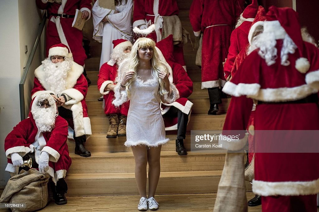 Students dressed as Santas and angels gather for their annual, pre-Christmas gathering at the cafeteria of the Studentenwerk Nord student support service on December 1, 2012 in Berlin, Germany. The students, mostly from Berlin Technical University (Technische Universitaet Berlin), have completed a Santa workshop and will visit company parties in December and families on Christmas Eve as a way to make a little money to help fund their studies.