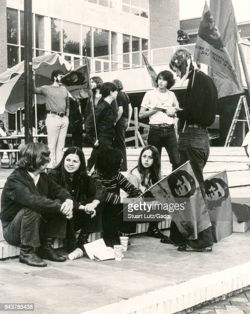 Students dressed in hippie attire sit on the steps of a campus building holding flags with the exhiled guerilla leader Che Guevara part of a student...