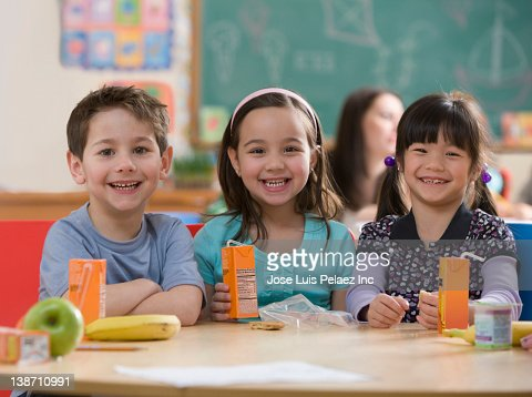 Students eating lunch together in classroom : Stock Photo
