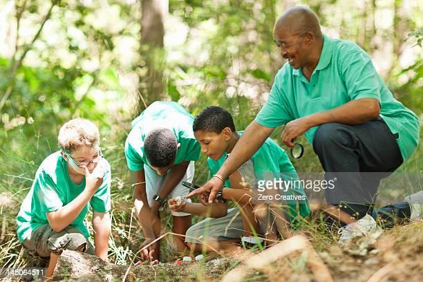 Studenten untersuchen Pflanzen mit Lehrer