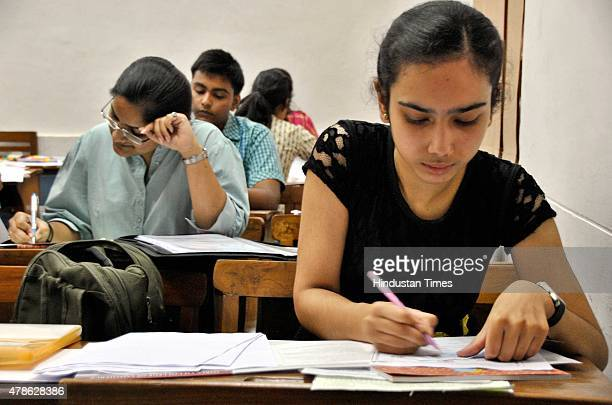 Students fill forms after the first cut off list came out for the new academic year 201516 at Delhi University on June 26 2015 in New Delhi India For...