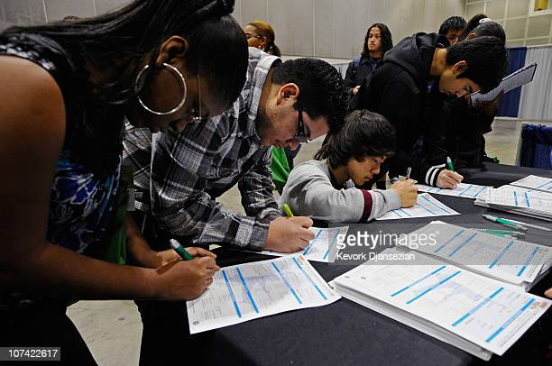 Students fill out applications for youth programs at Hire LA's Youth booth for a chance of finding a job as they attend Cash for College a college...