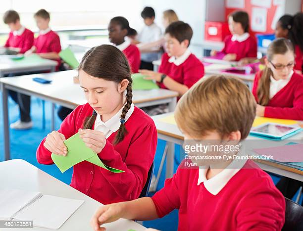 Students folding coloured paper in classroom
