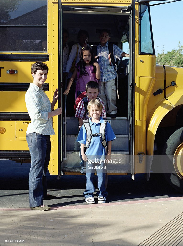 Students (5-7) forming line while exiting school bus, portrait : Stock Photo