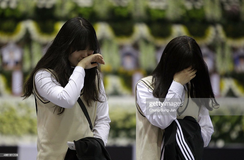 Students from Danwon high school weep after tribute at a group memorial altar for victims of sunken passengers ship at the Ansan Olympic Memorial Hall on April 23, 2014 in Ansan, South Korea. At the altar, Friends and relatives are able to pay tribute to those who have passed in the April 16 ferry disaster off of Jindo Island in South Korea. The confirmed death toll now reached 130, and more than 170 people are still missing, as reported.