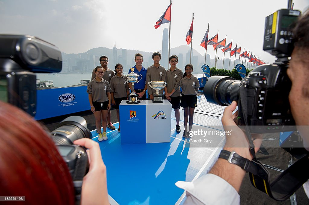Students from King George the V, ESF School, pose for photos with Todd Woodbridge and the AO trophys, over looking the Hong Kong skyline, during the Australian Open Trophy tour on October 22, 2013 in Hong Kong, Hong Kong.