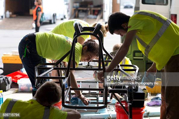 Students from Principia College of Elsah IL work on their solar car damaged by water in an overnight electrical fire that disabled several solar cars...