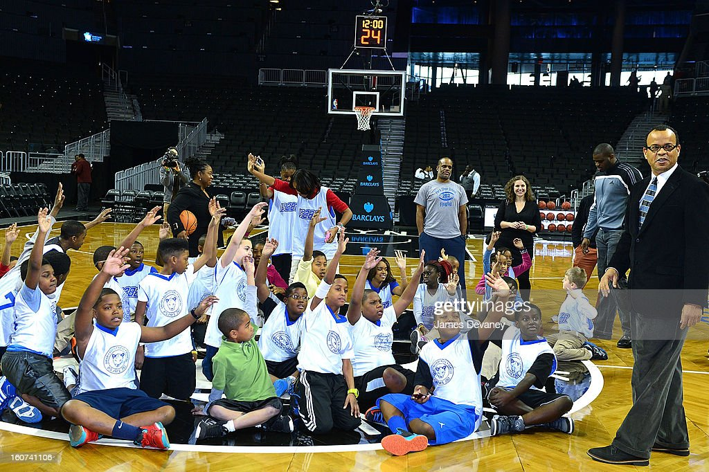 Students from P.S. 282 in Park Slope and Black Fives Foundation founder Claude Johnson honor the legacy of Brooklyn's African-American basketball history through the installation of six large-scale photographs of the Black Fives at Barclays Center on February 4, 2013 in the Brooklyn borough of New York City.