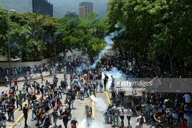 TOPSHOT Students from the Central University of Venezuela clash with riot police during a protest against Venezuelan Government in Caracas on May 4...
