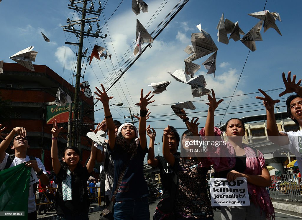 Students from the College Editor's Guild of the Philippines (CEGP) release paper planes into the air to signify that freedom of expression should not be pinned on the ground of different forms of human rights vilations, during a protest near the Malacanang Palace in Manila on November 22, 2012, a day prior to the third anniversary of the infamous November 23 massacre in Maguindanao province. Human Rights Watch on November 22 urged Philippine President Benigno Aquino to do more to break up private armed groups, three years after 58 people were killed in the country's worst political massacre.