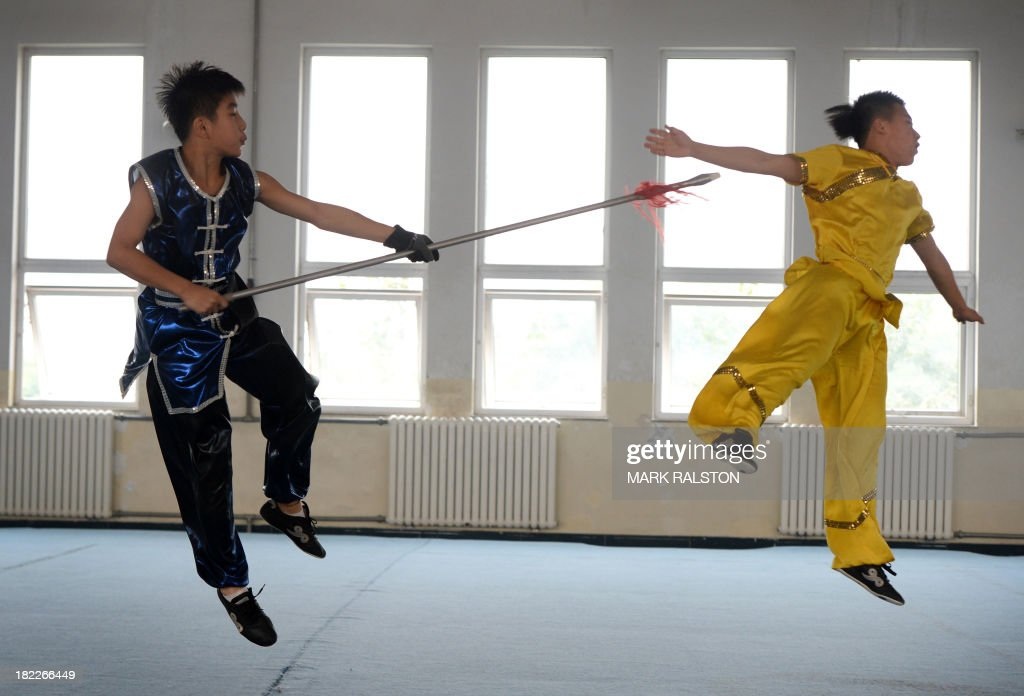 Students from the Huo Yuanjia Martial Arts School perform for visitors during a Wushu training session at their campus in Tianjin on September 29, 2013. The school which houses over 1500 martial arts students from all over China claims to have won over 1000 medals in International and national competitions. AFP PHOTO / Mark RALSTON