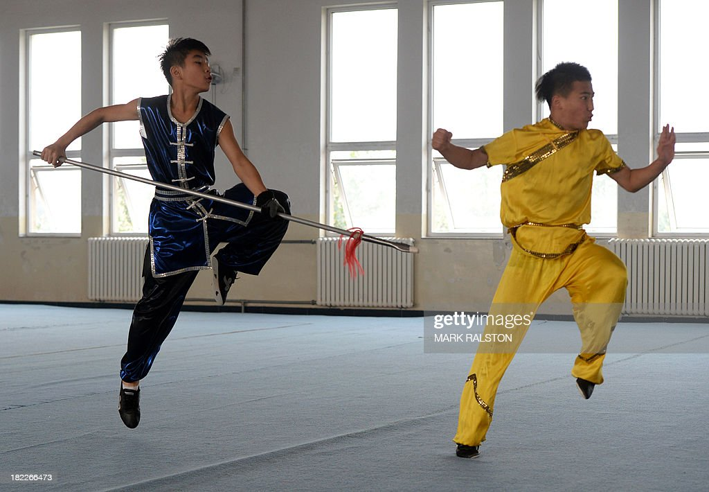 Students from the Huo Yuanjia Martial Arts School perform for visitors during a Wushu training session at their campus in Tianjin on September 29, 2013. The school, which houses over 1500 martial arts students from all over China, claims to have won over 1000 medals in international and national competitions. AFP PHOTO / Mark RALSTON