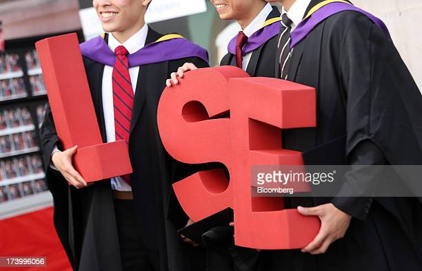 Students from the London School of Economics Political Science pose for a photograph with the letters reading 'LSE' during a ceremony for university...