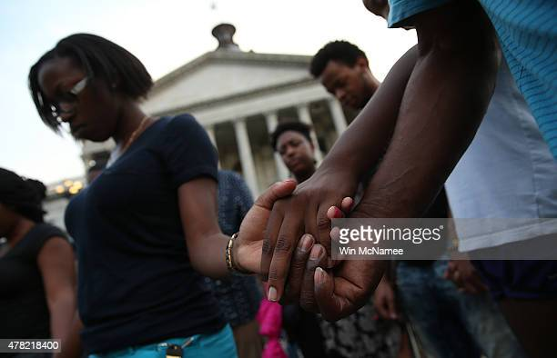 Students from the University of South Carolina and South Carolina State University link hands during a moment of silence for the nine victims of last...
