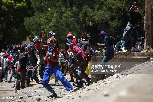 Students from the University of Witwatersrand throw stones against private security guards during clashes following a protest for free high education...