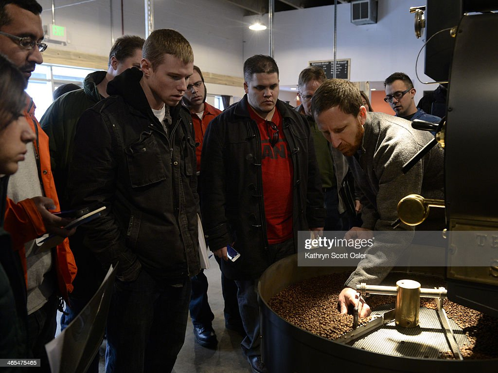 Students gather around as Andy Sprenger, right, owner of Sweet Bloom Coffee Roasters, leans in to examine some of the coffee beans just after they have been roasted. About 20 students from Metropolitan State University of Denver get a first-hand look at how coffee beans are roasted at the Sweet Bloom Coffee Roasters in Lakewood on Monday, Jan. 27, 2014.