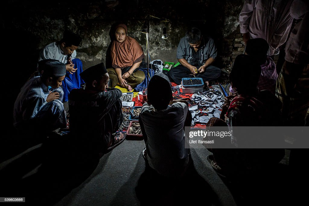 Students gather at a street vendor as they looking for prayer beads and other thing at the islamic boarding school Lirboyo during the holy month of Ramadan on June 10, 2016 in Kediri, East Java, Indonesia. The Islamic boarding school, Lirboyo, was founded by KH Abdul Karim in 1910, and known to be one of the largest traditional 'Pesantren' in Indonesia, with around 17,000 students in Kediri, East Java. Students at the Pesantren, also known as 'Santri', are separated from their families and spend their days studying Islamic scriptures, reading the Quran and learning Arabic in addition to other activities which begins with the morning prayer at 4am till midnight.